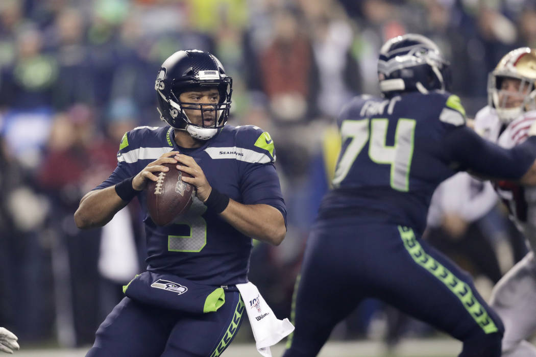 Seattle Seahawks quarterback Russell Wilson drops back to pass against the San Francisco 49ers ...