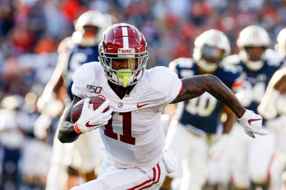Alabama wide receiver Henry Ruggs III (11) caries the ball against Auburn during an NCAA colleg ...