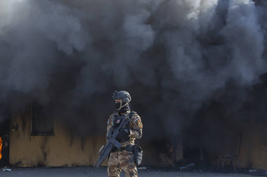 An Iraqi soldier stands guard in front of smoke rising from a fire set by pro-Iranian militiame ...