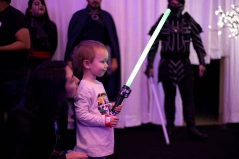 Daymien Freeth, 2, is in awe of his light saber as his mom, Theresa Freeth, encourages him at t ...