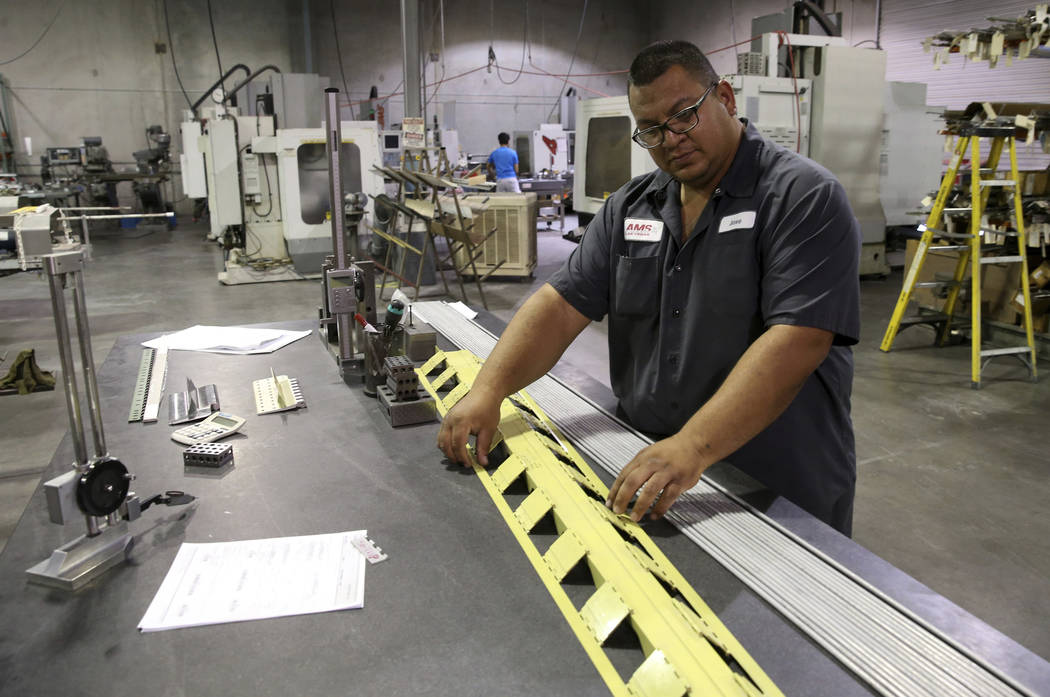 Facility Manager Jose Garcia shows a container release hinge with 70 individual hinges for a Bo ...
