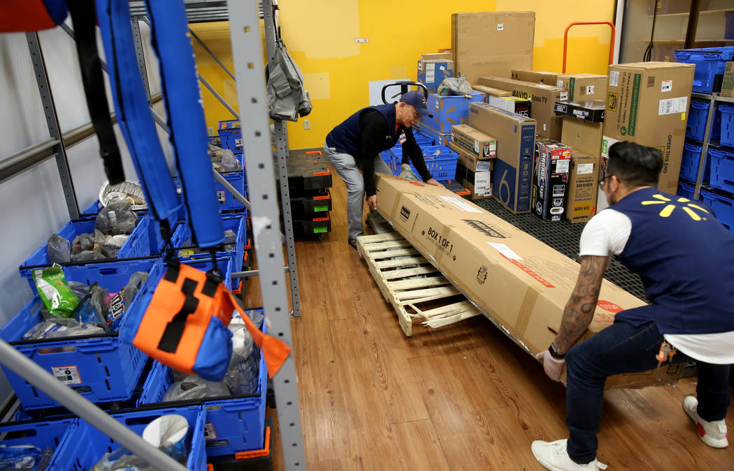 Personal shopper Nick Deleon, left, and department manager Richard Ramirez prepare a customer's ...