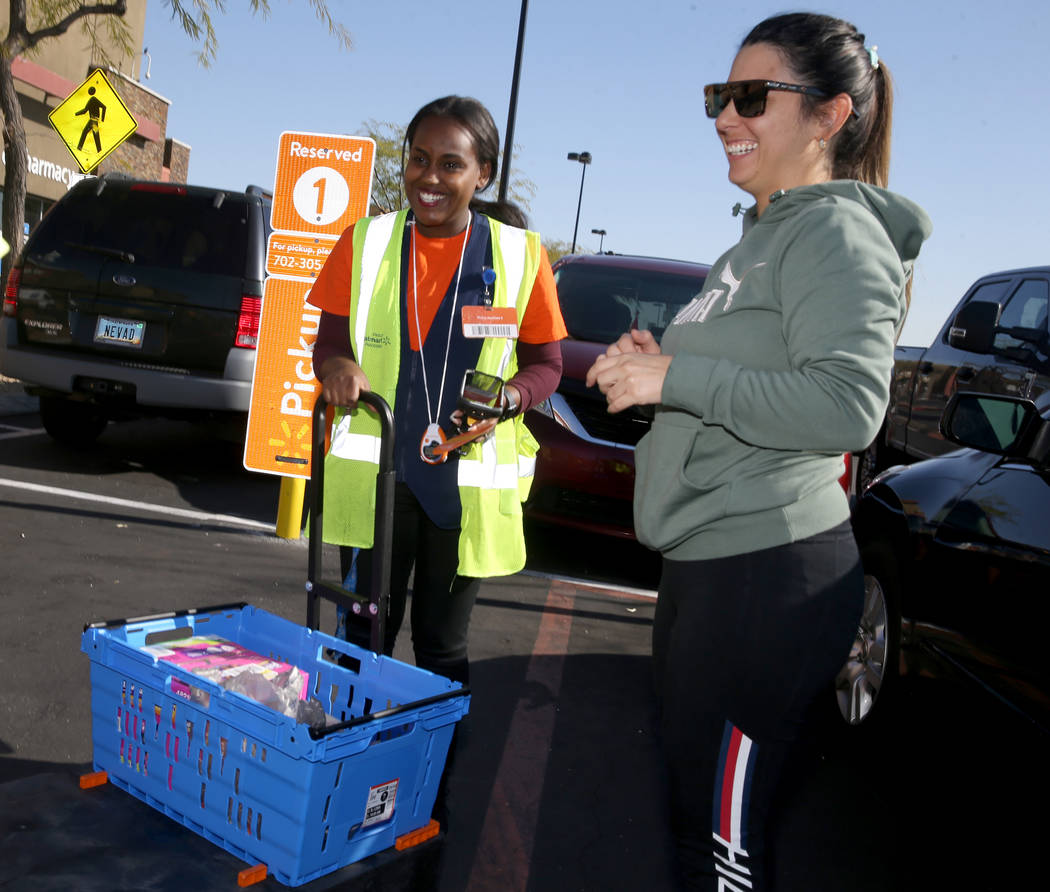Personal shopper Mety Woldeyes, left, delivers merchandise to customer Raquel Lobato at Walmart ...