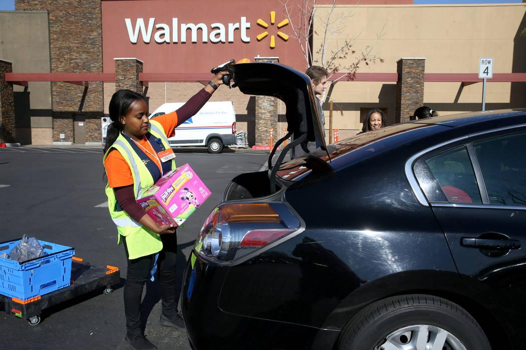 Personal shopper Mety Woldeyes loads a customer's curbside pickup order at Walmart at 7200 Arro ...