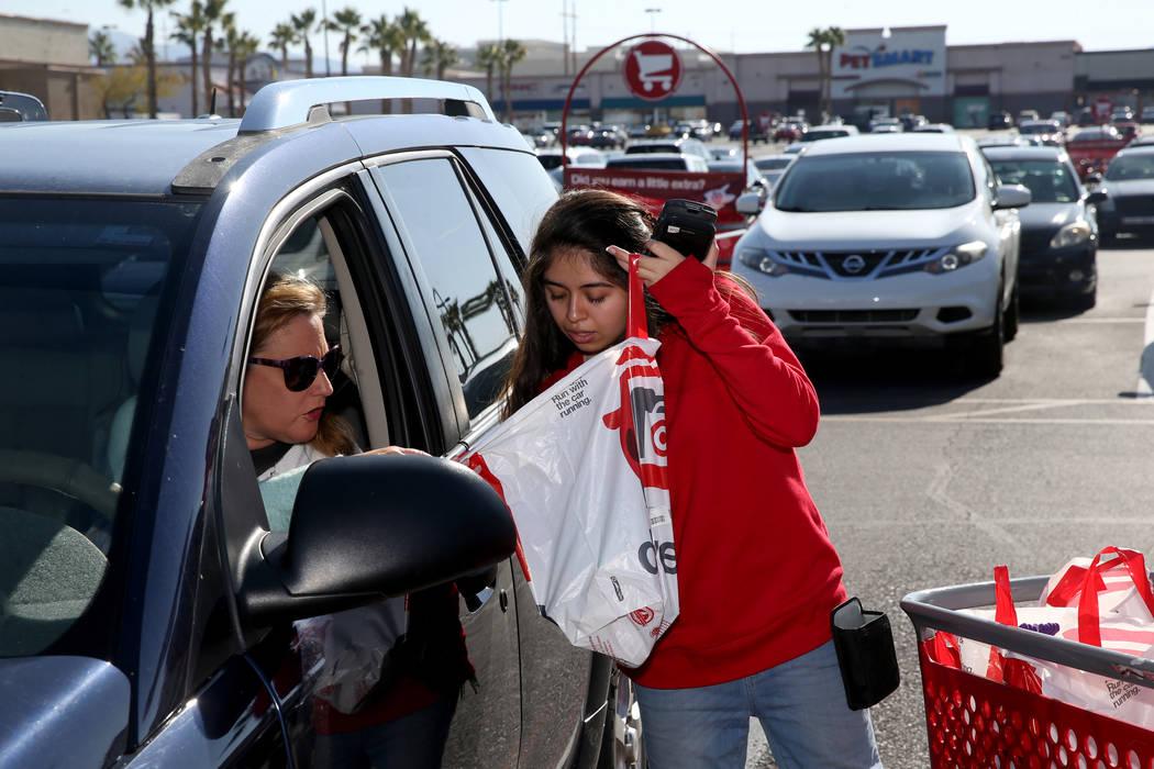 Guest service advocate Jessica De La Cruz delivers a curbside pickup order to Jessica Golonka a ...