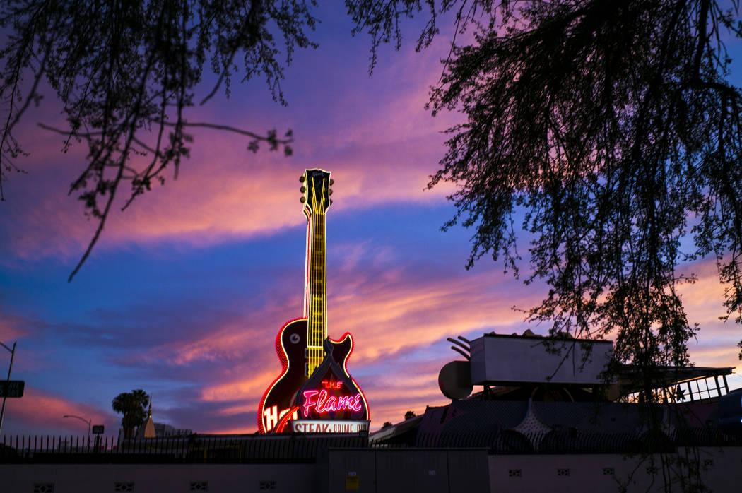 Vista de la guitarra del Hard Rock Cafe y los letreros de The Flame en el Neon Museum en el cen ...