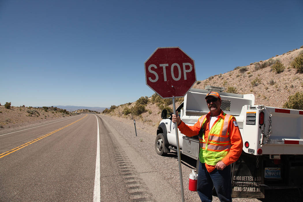A Nevada Department of Transportation employee readies to stop traffic near a clean up project. ...