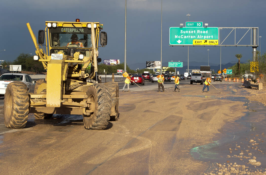 A Nevada Department of Transportation road crew works to clear the roadway at the I-215 eastbou ...
