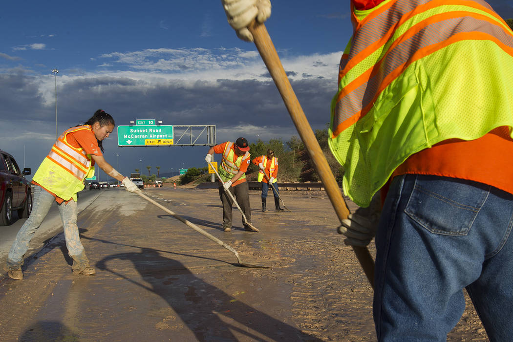 A Nevada Department of Transportation crew works to clear the roadway at the I-215 eastbound of ...