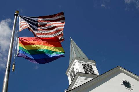 A gay pride rainbow flag flies along with the U.S. flag in front of the Asbury United Methodist ...