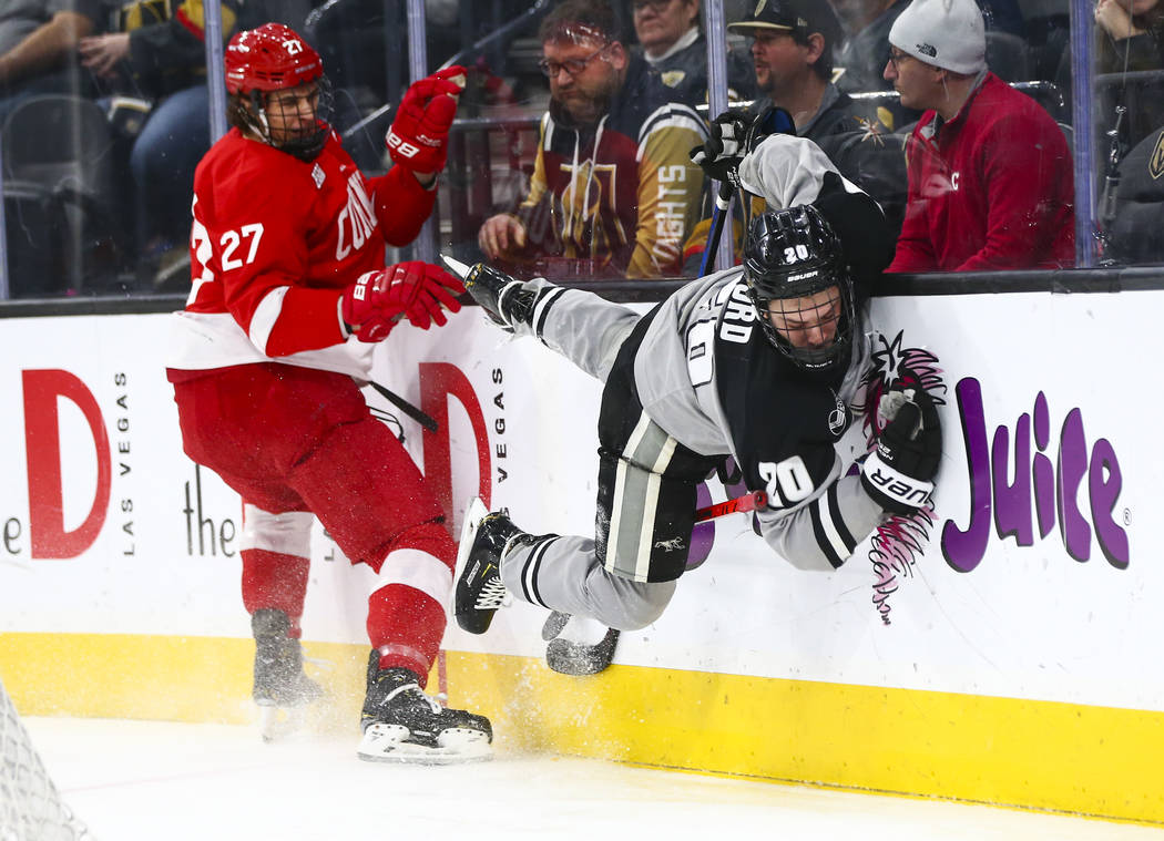 Providence Friars' Parker Ford (20) gets tripped up in front of Cornell Big Red's Morgan Barron ...
