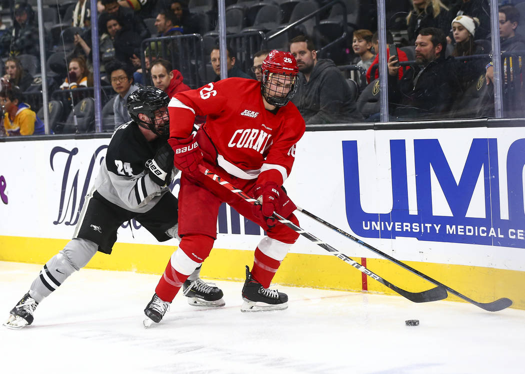 Cornell Big Red's Tristan Mullin (26) moves the puck in front of Providence Friars' Max Crozier ...