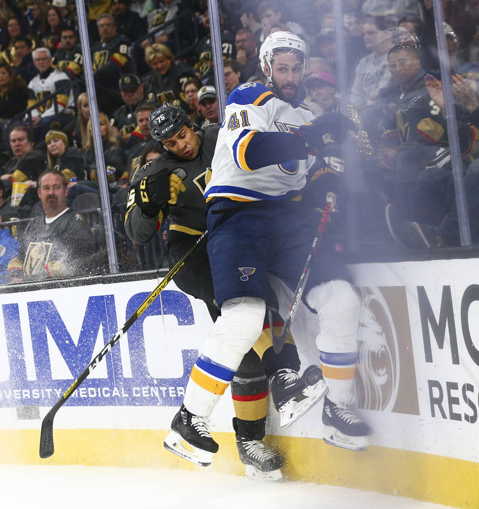 Golden Knights' Ryan Reaves (75) takes St. Louis Blues' Robert Bortuzzo (41) to the boards duri ...