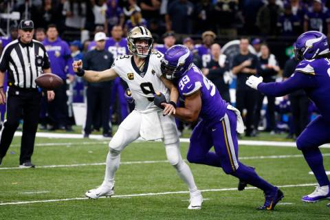New Orleans Saints quarterback Drew Brees (9) fumbles as he is hit by Minnesota Vikings defensi ...