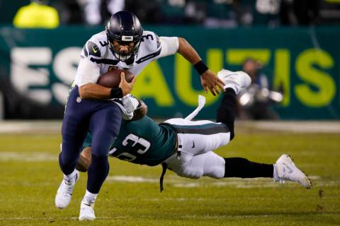 Seattle Seahawks' Russell Wilson (3) rushes past Philadelphia Eagles' Nigel Bradham (53) during ...