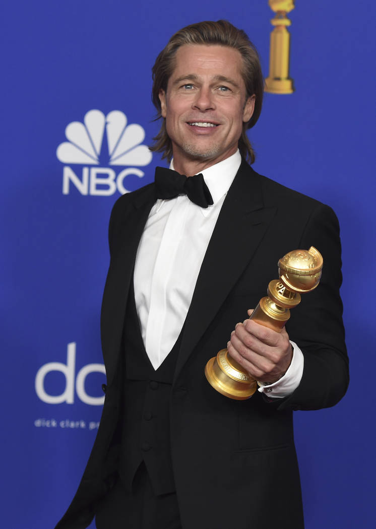 Brad Pitt poses in the press room with the award for best performance by an actor in a supporti ...