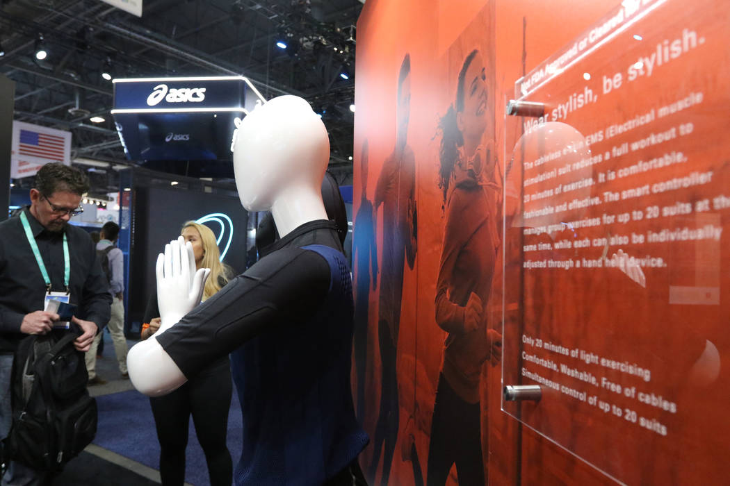 Attendees look at the E-Skin suit on display at the CES trade show at the Sands Expo Convention ...