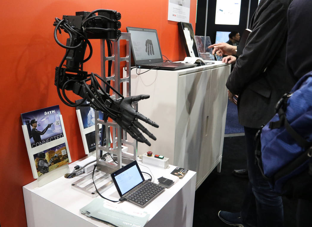 A robotic arm that shows how the E-Skin suit, a wearable fitness item, works on display at the ...