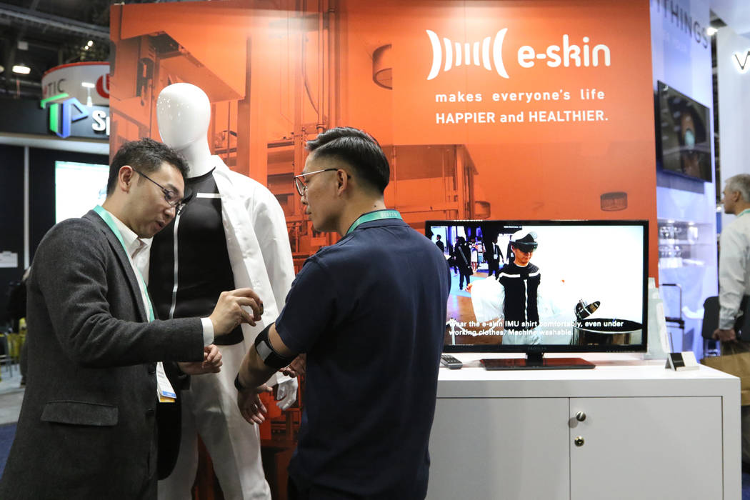 Attendees test how the E-Skin suit, a wearable fitness item, works at the CES trade show at the ...