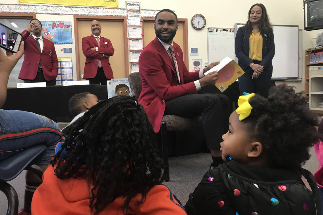 Evan Jackson Jr. with Kappa Alpha Psi reads to students at Booker Elementary School.