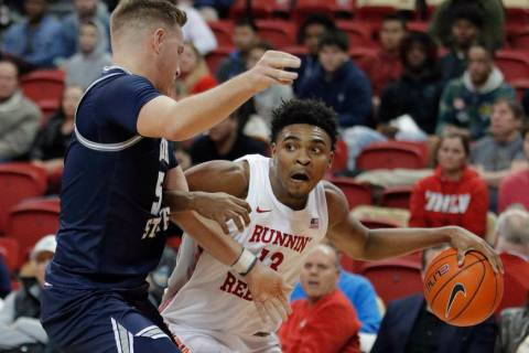 UNLV's Bryce Hamilton (13) drives around Utah State's Sam Merrill during the second half of an ...