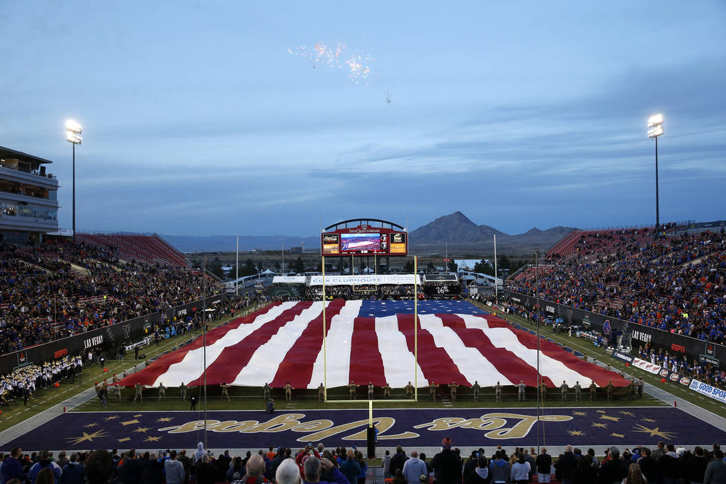 Airmen from Nellis Air Force Base unfurl an American flag in pregame ceremonies before the Las ...