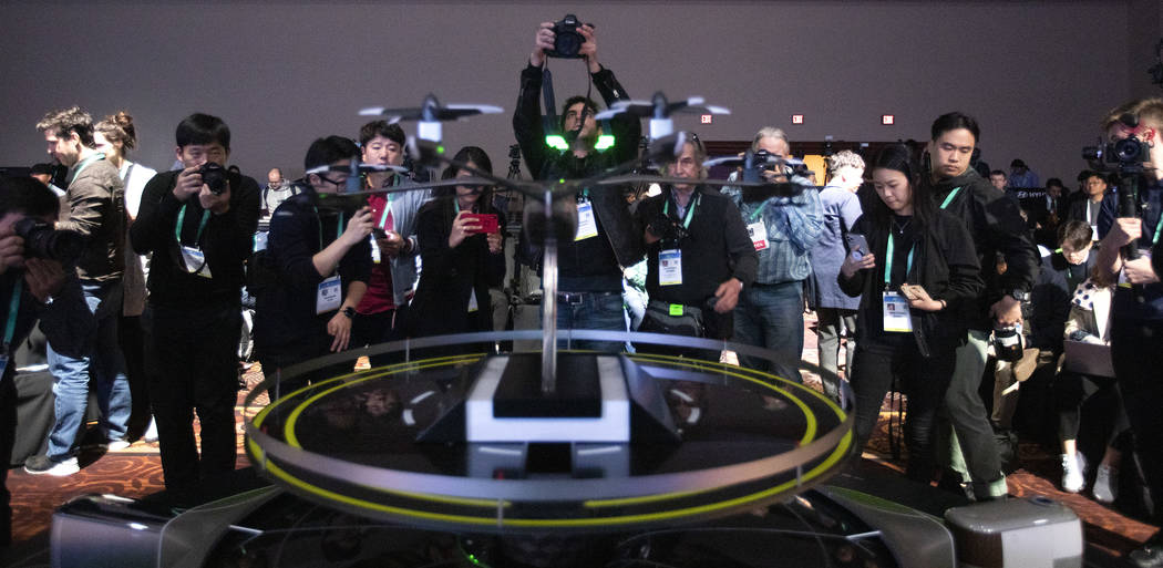 Members of the media record the new air taxi Hyundai created in partnership with Uber at the Hy ...