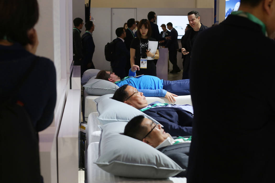 Individuals lay on the Sleep Number 360 Smart Bed during the first morning of CES 2020 at the S ...