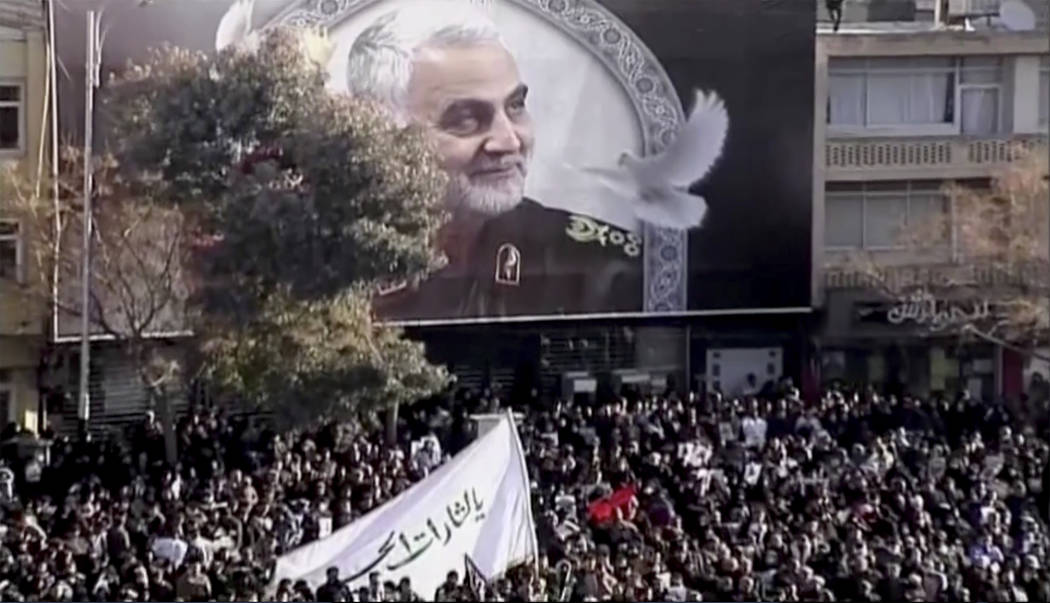 In this image made from a video, mourners gather to pay their respects to the slain Gen. Qassem ...