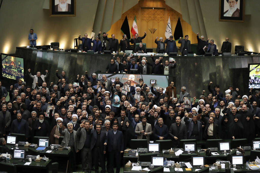 Iranian lawmakers chant slogans as some of them hold posters of Gen. Qassem Soleimani, who was ...
