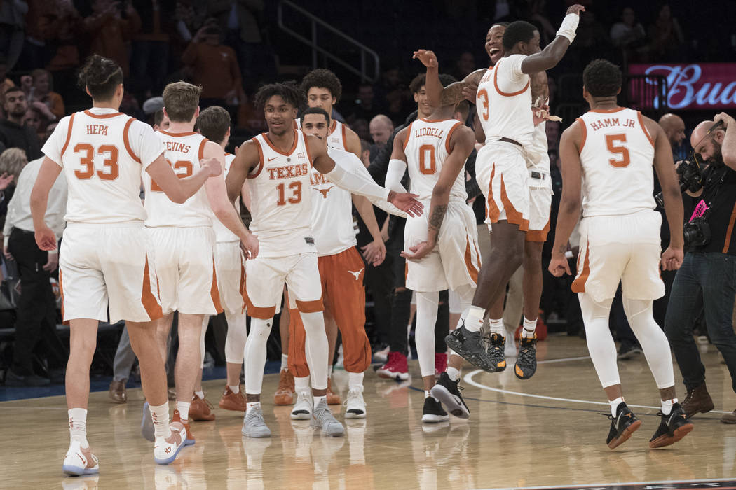 Texas players react after defeating Lipscomb in the championship basketball game of the Nationa ...