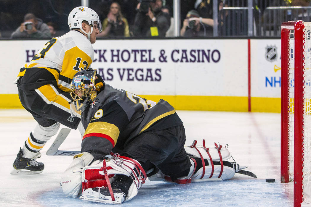 Pittsburgh Penguins' Brandon Tanev (13) scores on Vegas Golden Knights goaltender Marc-Andre Fl ...