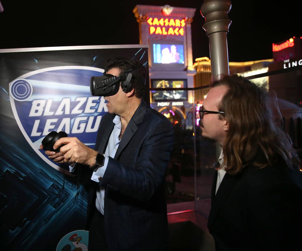 Las Vegas Review-Journal columnist John Katsilometes, left, tries virtual reality with Bryan Ch ...