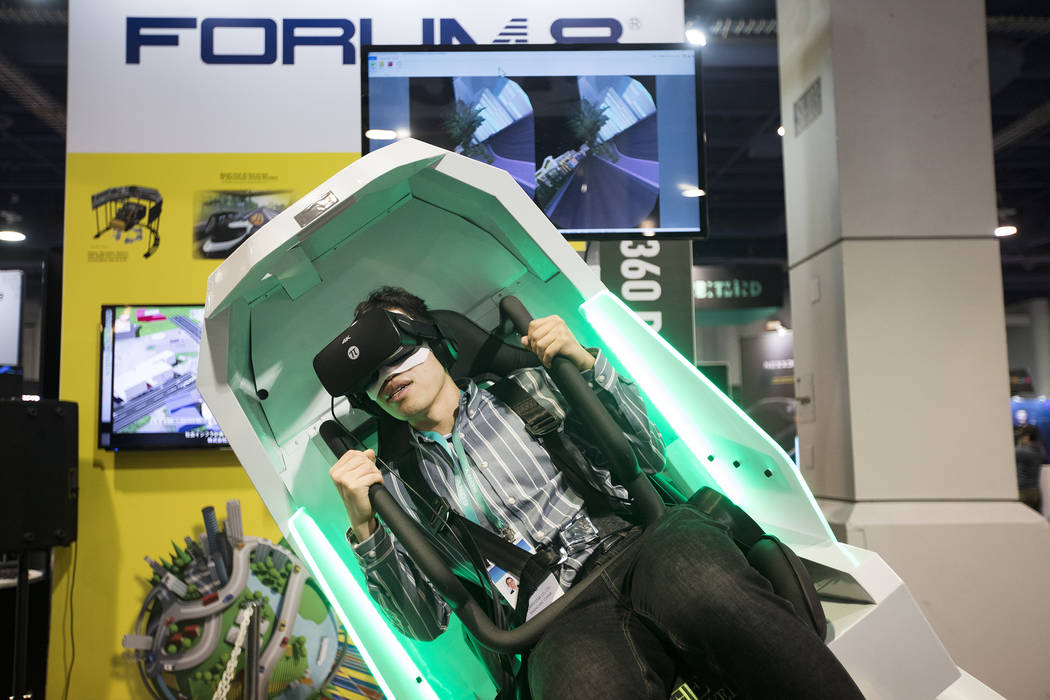 Shunjie Cai, of Singapore, tries out the VR360 by FORUM8, a ride and 360 degree simulator, at C ...