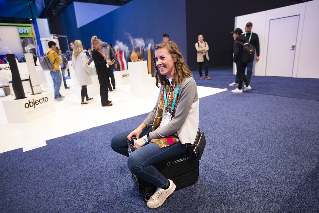 Chloe Richardson, from the U.K., tries out Modobag, a motorized carry-on at CES at the Las Vega ...