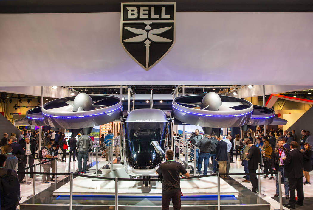 A worker dusts the front windshield of the new Bell Nexus 4EX air taxi concept on display in No ...