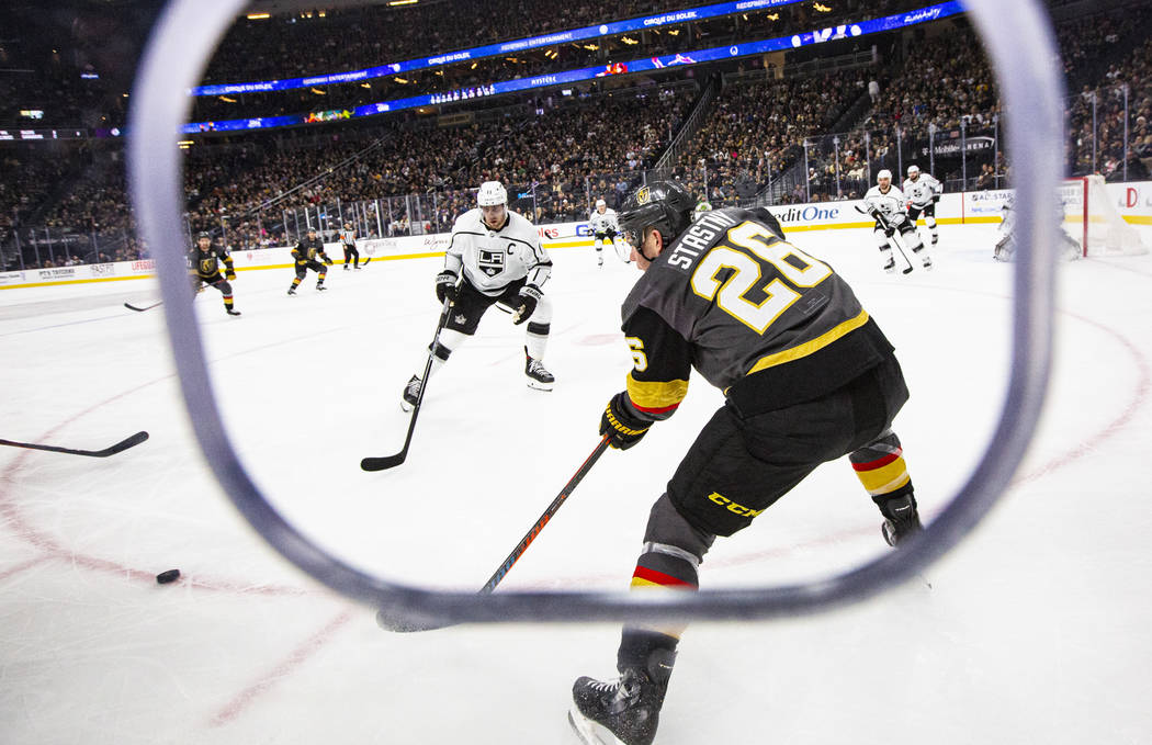 Golden Knights' Paul Stastny (26) sends the puck past Los Angeles Kings' Anze Kopitar (11) duri ...