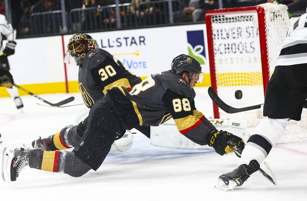 Los Angeles Kings' Alex Iafallo (19) sends the puck over Golden Knights' Nate Schmidt (88) and ...