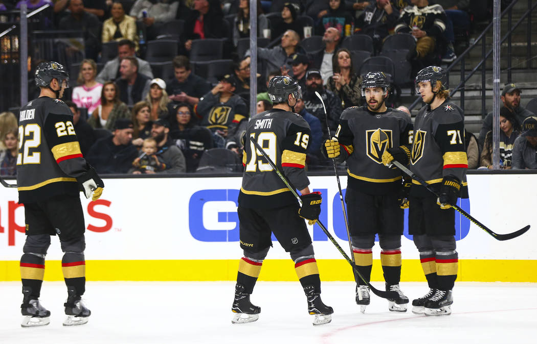 Golden Knights' Reilly Smith (19) talks with Chandler Stephenson, third from left, and William ...