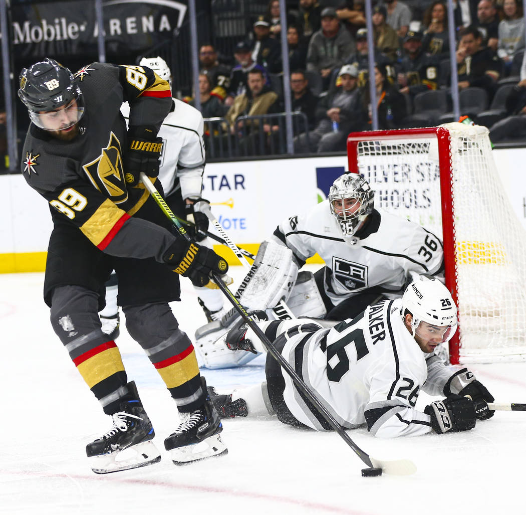 Golden Knights' Alex Tuch (89) moves the puck in front of Los Angeles Kings' Sean Walker (26) d ...