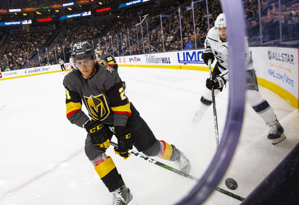 Golden Knights' Cody Eakin (21) moves the puck in front of Los Angeles Kings' Ben Hutton (15) d ...