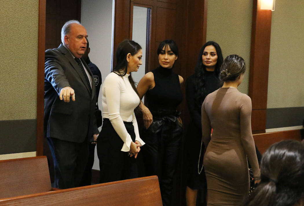 Four women, accused of an attack involving shoes at the Cosmopolitan, enter the courtroom with ...