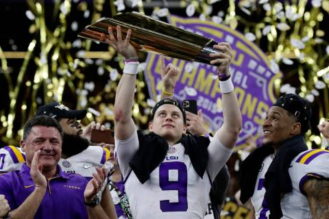 LSU quarterback Joe Burrow holds the trophy as safety Grant Delpit looks on after a NCAA Colleg ...