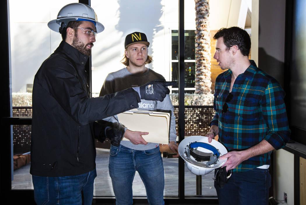 Golden Knights' Alex Tuch, left, talks with teammates William Karlsson, center, and Reilly Smit ...