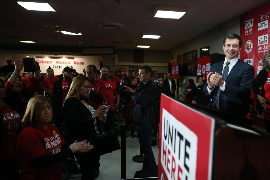 Democratic presidential candidate Pete Buttigieg, right, gets a standing ovation after particip ...