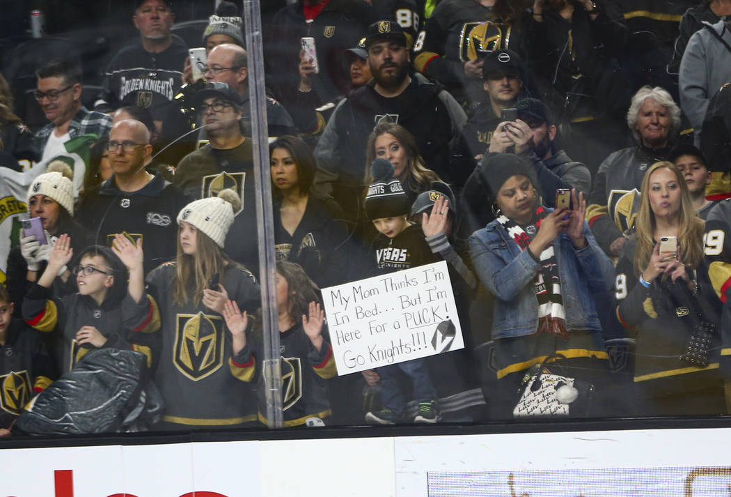 Golden Knights fans watch the team warm up before the start of an NHL hockey game against the C ...