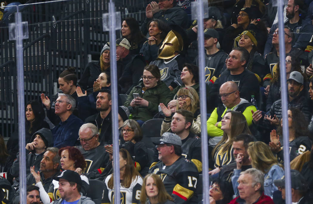 A Golden Knights fan wearing a mask watches the action during the first period of an NHL hockey ...