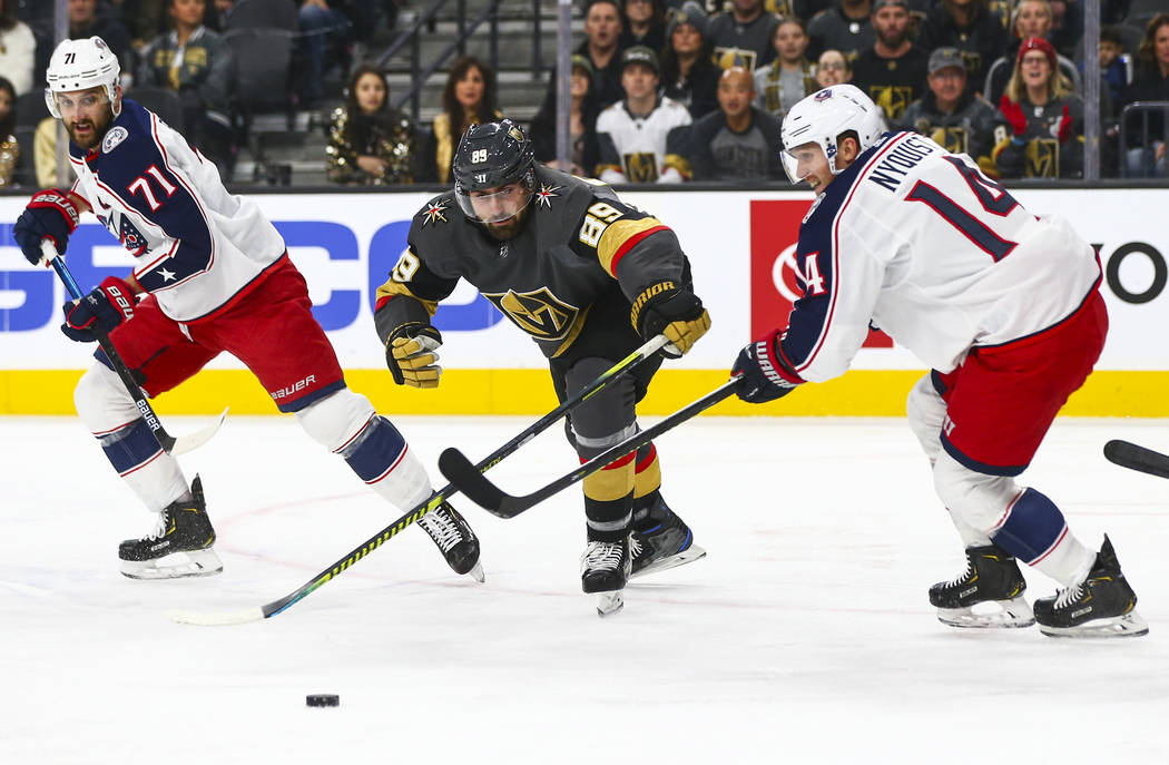 Golden Knights' Alex Tuch (89) chases after the puck between Columbus Blue Jackets' Nick Folign ...