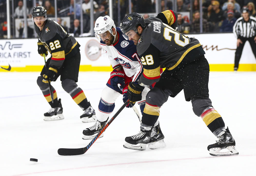 Golden Knights' William Carrier (28) battles for the puck against Columbus Blue Jackets' Nick F ...