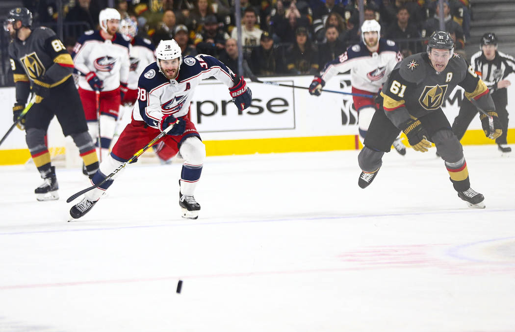 Columbus Blue Jackets' Boone Jenner (38) and Golden Knights' Mark Stone (61) chase after the pu ...
